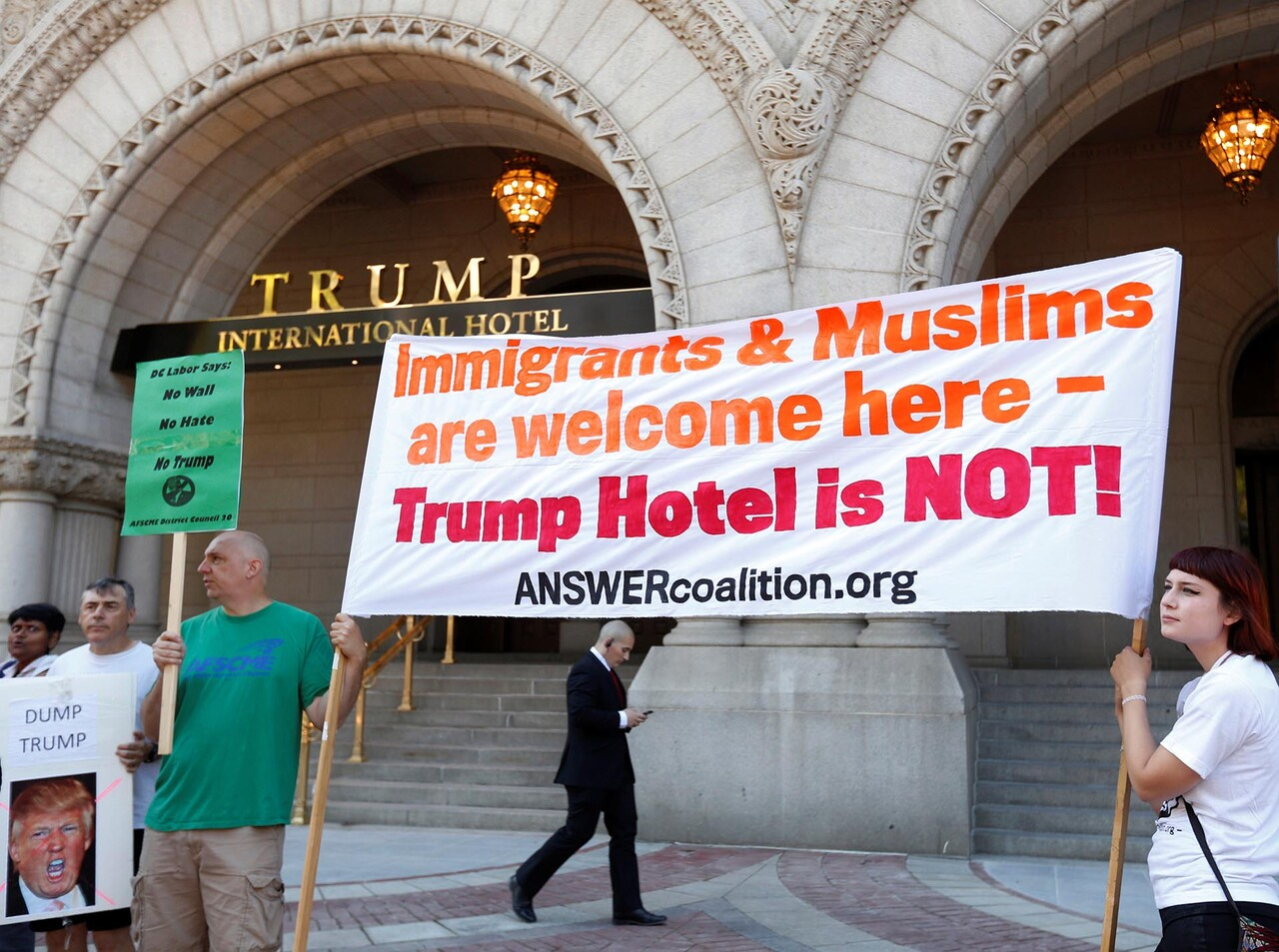 A security guard walks behind protesters holding signs outside the new Trump International Hotel on it' class=