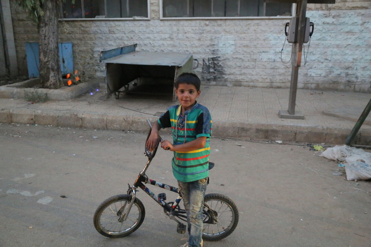 On 25 September 2016, a boy stands with his bicycle in Madaya in the Syrian Arab Republic. UNICEF participated in UN-interagency convoys to four towns, delivering urgently needed humanitarian assistance to 60,000 people. Under the so-called Four Town Agreement, convoys delivered supplies to people in Madaya and Zabadani in Rural Damascus and Foah and Kefraya in Idlib governorate. UNICEF delivered health, nutritional supplements, hygiene supplies, educational supplies and childrenÕs clothes for 20,000 people in Madaya and Zabadani Ð and the same supplies for 10,000 people in Foah and Kafraya. In Madaya, UNICEF screened children for malnutrition and supported local health teams. The convoys were the first time UNICEF and our partners have been able to access the four towns since late April.
