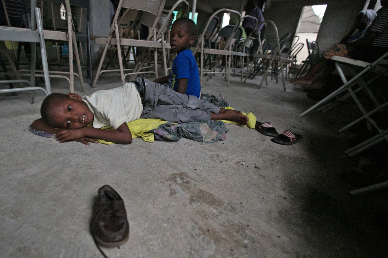 On 3 October 2016, a boy and his brother rest in a church in Croix des Bouquets, a neighbourhood on the east of Port-au-Prince where they are staying to find some protection from hurricane Matthew. The hurricane is expected to hit the neighbourhood where they live, Cite Soleil, which is a populated slum area right by the ocean in Port-au-Prince with houses made out of shacks and canals filled with garbage. On 4 October 2016, more than 4 million children may be exposed to the damage of Hurricane Matthew, UNICEF said as the Category 4 storm made landfall on the impoverished Caribbean island. Strong winds and torrential rains are battering the island, raising the risk of floods and landslides. The airport remains closed and children have been told to stay home from school – particularly as many schools are being used to shelter evacuees.  Haiti is still recovering from the 2010 earthquake, with 55,000 people still living in shelters. The southern coast, where the storm is expected to hit the most, is one of the poorest and most densely populated parts of the country. In a country where less than 1 in 5 people in rural areas have access to improved sanitation and 40 per cent of people use unsafe water sources, it is feared that the hurricane will worsen an already precarious situation. Cholera is endemic and with more than 27,000 suspected cholera cases reported already this year – an estimated one third of them children – any damage to water and sanitation infrastructure or largescale displacement could put children and families at greater risk of infection. UNICEF is working to support the Government's humanitarian response. Life-saving supplies for 10,000 people are in place and ready to be distributed to the most affected families in the worst hit areas. They include water bladders and chlorination tablets, hygiene kits and mosquito nets.