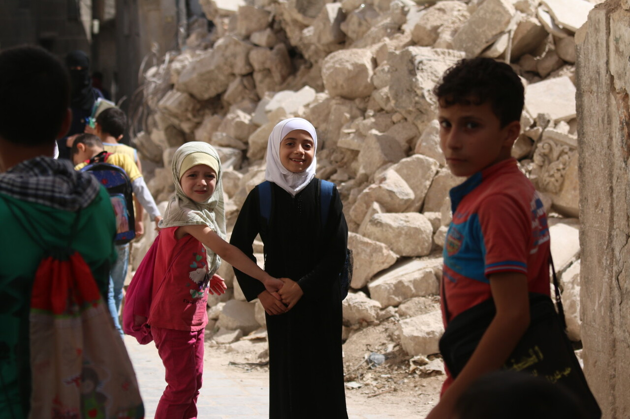 """On 21 September 2016 in eastern Aleppo in the Syrian Arab Republic, Judy (white head scarf), 9, and her schoolmates return from the first day of school passing the rubble of nearby houses.  """"I go to school every day, except for the times when I hear the planes,"""" Judy explains.  """"I want the road to reopen so I can go see my brother who lives in another city and just got married. I haven't even met his wife yet,"""" says Judy.  Instead, the road remained closed due to heavy bombardment and shelling. In Judy's neighborhood, electricity is largely unavailable as there is a fuel shortage.   One in four schools are not functioning in the Syrian Arab Republic because they have been damaged, destroyed, or serve as shelters for displaced families or are in use for military purposes.  Over two million children across the country are not able to go back to learning, while another 400,000 children are at risk of dropping out, due to heavy violence, lack of safe learning environments and displacement.  More than 52,000 teachers have left their jobs.  Two decades of investment in learning has been wiped out, as some children have lost up five years of their education, while others have never been to school.   UNICEF is supporting more than 1,200 dedicated young volunteers to conduct a door-to-door campaign to map the numbers and situations of out-of-school children, while reaching out to parents with information about the simplified school enrollment processes and the right to have an education.  Also recently launched is a back-to-learning campaign that aims to reach 2.5 million children in the country, including 154,000 living in besieged and hard-to-reach areas. UNICEF will be providing educational materials, school bags and stationery.  A social mobilization campaign encourages parents to send their children to school or benefit from alternative learning opportunities where schools are no longer functioning.  As part of that campaign, social media, radio and televi"""