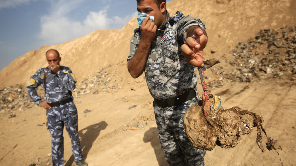 EDITORS NOTE: Graphic content / A member of the Iraqi forces holds a skull they dug up from a mass grave they discovered in the Hamam al-Alil area on November 7, 2016 after they recaptured the area from Islamic State (IS) group jihadists during the ongoing operation to retake Mosul, the last IS-held Iraqi city. Iraqi investigators carried out an initial examination of a mass grave site discovered in an area south of Mosul that was recently retaken from the Islamic State group.  / AFP PHOTO / AHMAD AL-RUBAYE