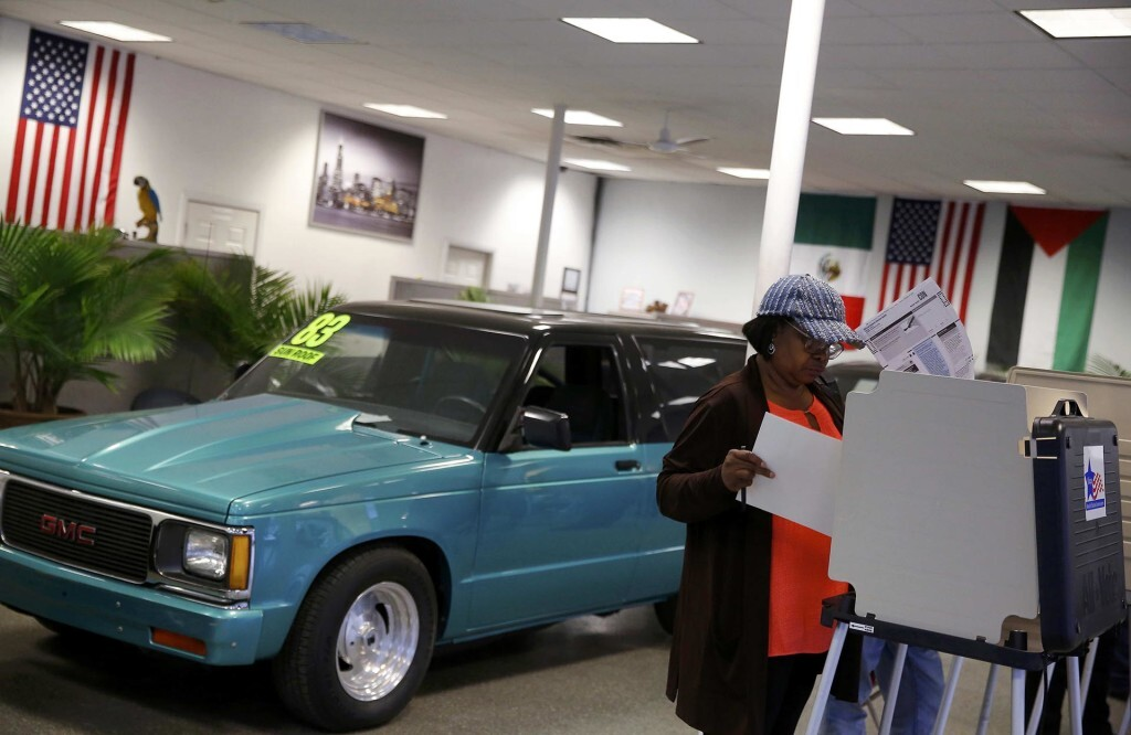 A voter looks over her ballot for the U.S. presidential election at Sam' class=