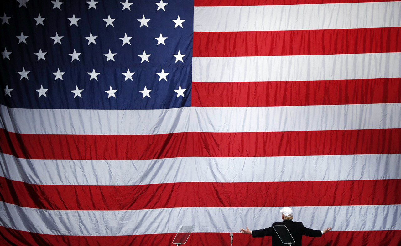 FILE - In this Sunday, Nov. 6, 2016 file photo, Republican presidential candidate Donald Trump turns to face the U.S. flag at a campaign rally in Sterling Heights, Mich. (AP Photo/Paul Sancya)
