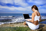 Brunette girl working over laptop computer on the beach.