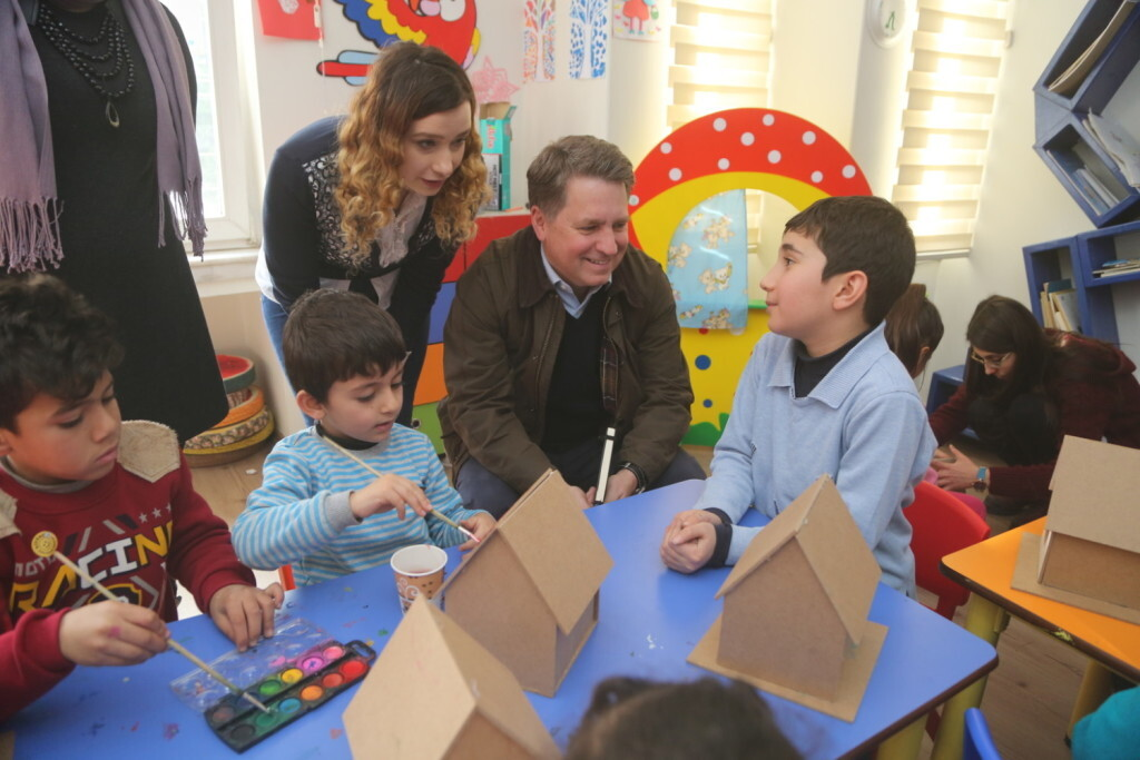 """On 16 January 2017, UNICEF Executive Director Justin Forsyth speaks to Syrian children at Al Farah centre in Gaziantep, southern Turkey. Al Farah is a one-stop shop for Syrian families living outside refugee camps to register for assistance, attend Turkish language classes, and receive non-food items. Children can participate in recreational activities and receive psychosocial support. In January 2017, over 40 per cent of Syrian refugee children in Turkey missing out on education, despite massive increase in enrolment rates. Nearly half a million Syrian refugee children are currently enrolled in schools across Turkey. But despite a more than 50 per cent increase in enrolment since last June, over 40 per cent of children of school-going age – or 380,000 child refugees – are still missing out on an education.  Turkey is home to more than 1.2 million child refugees, making it the top child refugee hosting country in the world.  In partnership with the Government of Turkey, UNICEF is helping strengthen education systems, increase access to learning and improve the quality of inclusive education for Syrian and vulnerable Turkish children.  """"For the first time since the start of the Syrian crisis, there are more Syrian children in Turkey attending class than there are out of school,"""" said UNICEF Deputy Executive Director Justin Forsyth, speaking after a visit to UNICEF programmes in southern Turkey.  """"Turkey should be commended for this huge achievement. But unless more resources are provided, there is still a very real risk of a 'lost generation' of Syrian children, deprived of the skills they will one day need to rebuild their country."""" Since 2013, UNICEF has helped build, renovate or refurnish nearly 400 schools, and trained some 20,000 Syrian volunteer teachers. Approximately 13,000 teachers receive monthly incentives.  Efforts are also under way to include Syrian children in a national programme that grants cash allowances to vulnerable families"""