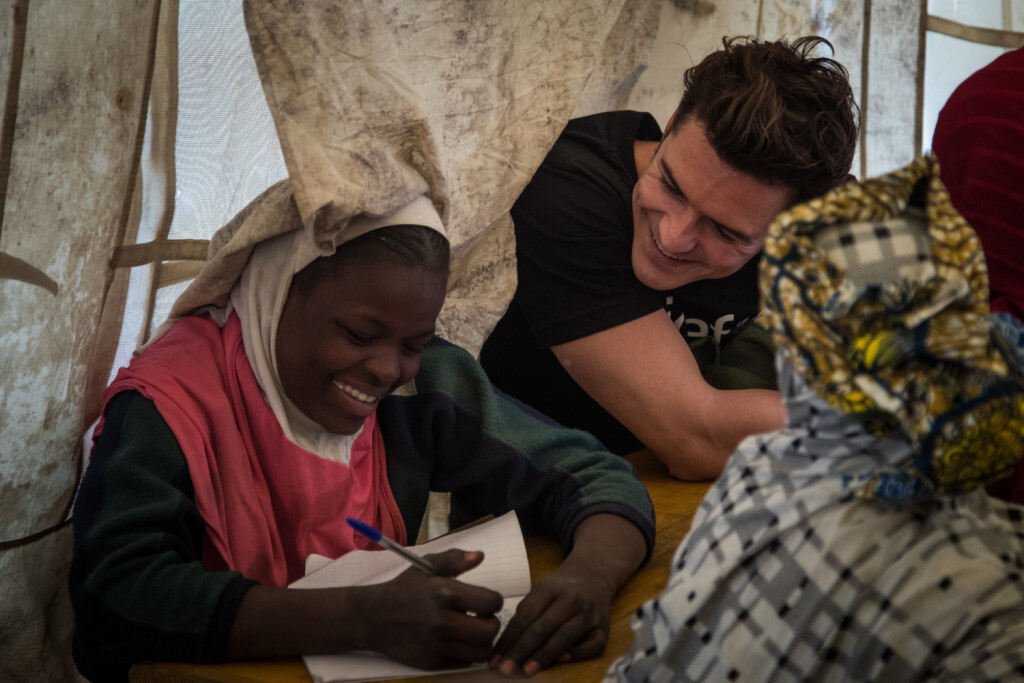 "UNICEF Goodwill Ambassador Orlando Bloom (right) speaks with twelve-year-old Aicha Gabtchami, a fifth grade student at a temporary learning space at a camp for internally displaced people in Ngagam, near Diffa, Niger, Friday 17 February 2017. Aicha, who was displaced from Barwa, Niger near Lake Chad, came to Ngagam camp with her mother and grandmother by foot. The family were forced to flee after being threatened by Boko Haram members, who killed others around them as they fled. Her uncle was killed while in the bush. Aicha's father, who had already left Barwa, was also killed by Boko Haram insurgents. Attending classes at the school makes Aicha feel better, ""more comfortable"" as she puts it. In late February 2017, UNICEF Goodwill Ambassador Orlando Bloom travelled to Diffa, south-east Niger, to highlight the ongoing humanitarian crisis in West Africa's Lake Chad Basin (Niger, Nigeria, Chad, Cameroon). Boko Haram violence has caused huge population displacements, leaving hundreds of thousands of children in a critical situation, out of education and at risk of malnutrition. Across the four countries, 2.3 million people are now displaced, making this one of the fastest growing displacement crises in Africa. The Diffa region currently hosts over 240,000 internally displaced people, refugees and returnees—including 160,000 children. UNICEF is providing safe environments for children in Niger and across the region to play, as well as helping them return to school, and training teachers to identify and support children traumatised by the increasing violence in the region. UNICEF is also providing lifesaving treatment for children suffering from severe malnutrition. ""This visit has been extremely moving. Every single child I met is affected by this conflict and in desperate need of basic services such as clean water, psychological care and education to help them recover from the atrocities they have suffered and witnessed. They deserve a childhood,"" said"