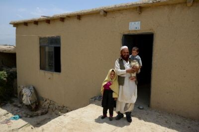 Mohammed-Jan, de 51 años, junto a sus hijos, frente a su casa en Pahjman. Retornaron hace poco a la capital afgana, Kabul, desde el campamento de refugiados en el que vivían en Pakistán. (© ACNUR/UNHCR/ Sebastian Rich)