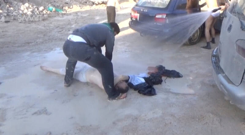 ATTENTION EDITORS - VISUAL COVERAGE OF SCENES OF INJURY OR DEATH A still image taken from a video posted to a social media website on April 4, 2017, shows a man lying on the ground and being sprayed with water, said to be in the town of Khan Sheikhoun, after what rescue workers described as a suspected gas attack in rebel-held Idlib, Syria. Social Media Website via Reuters TV ATTENTION EDITORS - THIS IMAGE HAS BEEN SUPPLIED BY A THIRD PARTY. IT HAS BEEN CHECKED BY REUTERS' SOCIAL MEDIA TEAM AND REVIEWED BY A SENIOR EDITOR. REUTERS IS CONFIDENT THE EVENTS PORTRAYED ARE GENUINE TEMPLATE OUT