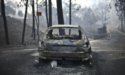 A picture taken on June 18, 2017 shows a burnt car on a road after a wildfire in Pedrogao, in central Portugal. A wildfire in central Portugal killed at least 57 people and injured 59 others, most of them burning to death in their cars, the government said on June 18, 2017. Several hundred firefighters and 160 vehicles were dispatched late on June 17 to tackle the blaze, which broke out in the afternoon in the municipality of Pedrogao Grande before spreading fast across several fronts.    / AFP PHOTO / PATRICIA DE MELO MOREIRA