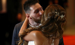 Argentine soccer player Lionel Messi and his wife Antonela Roccuzzo kiss as they pose at their wedding in Rosario, Argentina