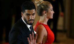 Barcelona FC's Luis Suarez, teammate of Argentine soccer player Lionel Messi, gestures next to his wife Sofia Balbi as they pose for photographers as they arrive at the wedding of Messi and Antonela Roccuzzo in Rosario