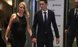 Paris Saint Germain's footballer Argentine Angel di Maria poses with his wife on a red carpet during Argentine football star Lionel Messi and Antonella Roccuzzo's wedding in Rosario, Santa Fe province, Argentina on June 30, 2017.