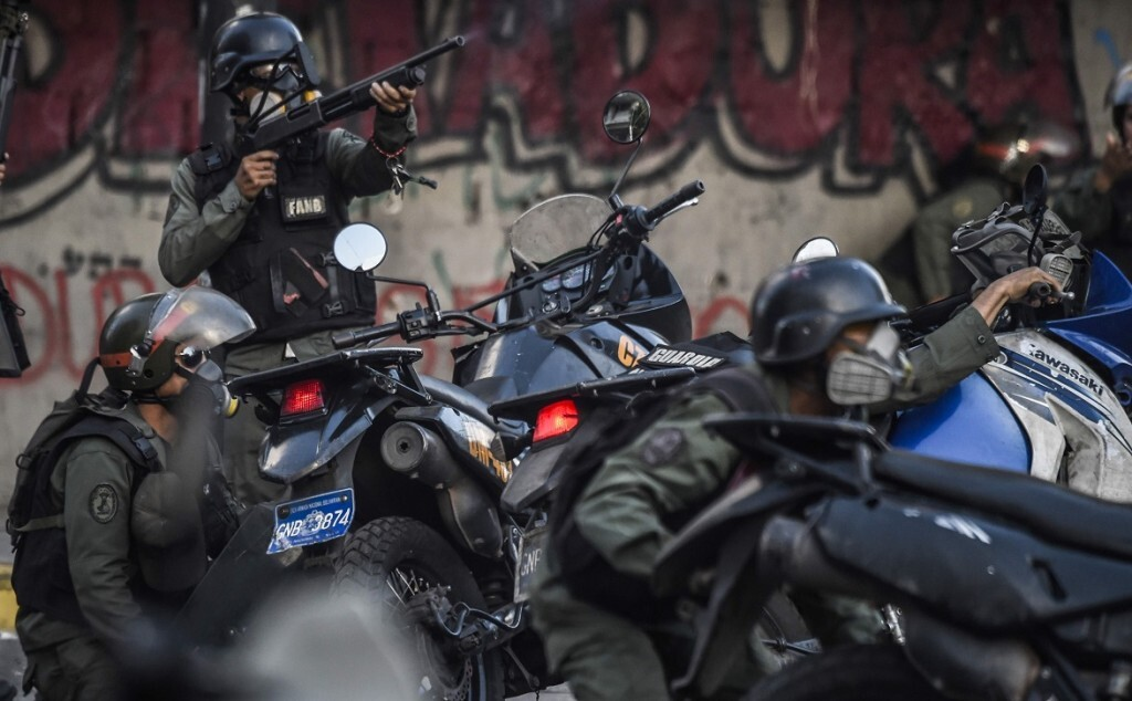 TOPSHOT - Venezuelan National Guard motorcyclists take cover upon coming under fire during a confuse skirmish in Caracas on July 30, 2017. Deadly violence erupted around the controversial vote, with a candidate to the all-powerful body being elected shot dead and troops firing weapons to clear protesters in Caracas and elsewhere. / AFP / JUAN BARRETO