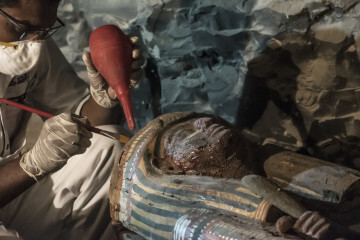 "A picture taken on September 9, 2017 shows Egyptian archaeologist restoring a wooden sacrophagus at a newly-uncovered ancient tomb for a goldsmith dedicated to the ancient Egyptian god Amun, in the Draa Abul Naga necropolis on the west bank of the ancient city of Luxor, which boasts ancient Egyptian temples and burial grounds. The finds at the tomb of ""Amun's Goldsmith, Amenemhat"", which dates back to the New Kingdom (16th to 11th centuries BC), also contained a sculpture carved into a recess of him seated beside his wife, with a portrait of their son painted between them, in addition to another 150 small funerary statues carved in wood, clay and limestone. A burial shaft in the tomb led to a chamber where the archaeologists discovered mummies, funerary statues and masks, the antiquities ministry said. / AFP PHOTO / KHALED DESOUKI"