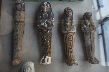 "A picture taken on September 9, 2017 shows small funerary statues carved in wood, clay and limestone recovered at the site of a newly-uncovered ancient tomb for a goldsmith dedicated to the ancient Egyptian god Amun, in the Draa Abul Naga necropolis on the west bank of the ancient city of Luxor, which boasts ancient Egyptian temples and burial grounds. The finds at the tomb of ""Amun's Goldsmith, Amenemhat"", which dates back to the New Kingdom (16th to 11th centuries BC), also contained a sculpture carved into a recess of him seated beside his wife, with a portrait of their son painted between them. A burial shaft in the tomb led to a chamber where the archaeologists discovered mummies, funerary statues and masks, the antiquities ministry said. / AFP PHOTO / KHALED DESOUKI"
