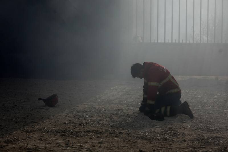 -FOTODELDIA- epa06268200 A firefighter kneels on the ground duringg a fire in Vila Nova de Poiares, Lousa, Portugal, 15 October 2017. The National Civil Protection Authority (ANPC) said it 'was the worst day of the year in terms of fires', having exceeded 300 forest fires. EPA/PAULO CUNHA