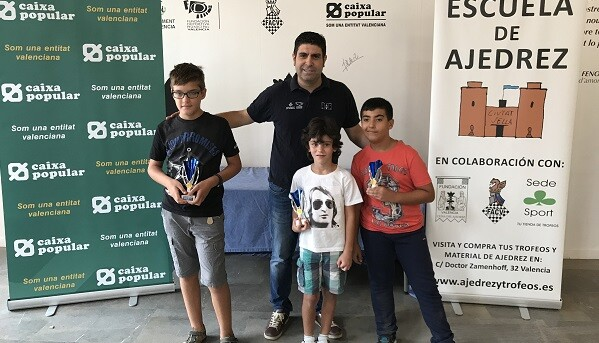 El coordinador de la EEDD de Ajedrez, Román Beltrán junto a los tres primeros clasificados.