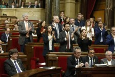 Delegates applaud after a speech as Catalan President Carles Puigdemont, bottom left, smiles during a session inside the Catalan parliament in Barcelona, Spain, Friday, Oct. 27, 2017. Catalan separatist lawmakers have filed a motion to hold a vote in the upcoming regional parliament session on whether to establish a republic independent of Spain. (AP Photo/Manu Fernandez)