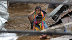 A policeman carries a young girl as he wades through a flooded street in Cagayan City on December 22, 2017, after the Cagayan River swelled caused by heavy rains brought by Tropical Storm Tembin. Three people have been killed and six others are missing as a tropical storm struck the southern Philippines on December 22, unleashing floods and landslides across a region of 20 million people, officials said. / AFP PHOTO / Josep DEVEZA