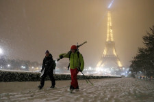 Men walk with skis on a snow-covered path near the Eiffel Tower in Paris, as winter weather with snow and freezing temperatures arrive in France, February 6, 2018. Picture taken February 6, 2018.  REUTERS/Gonzalo Fuentes