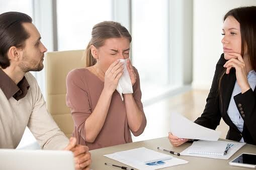 Young businesswoman holding handkerchief sneezing during meeting with colleagues