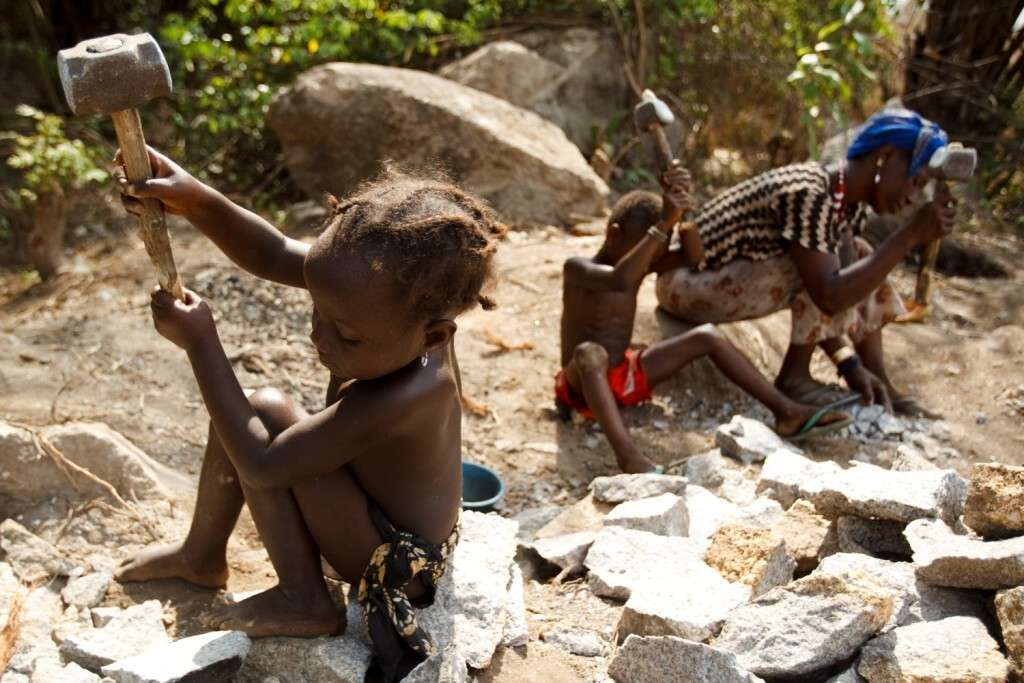 A woman and children work breaking stones with hammers at a quarry near Makeni, Bombali district, Sierra Leone on Thursday March 24, 2011.