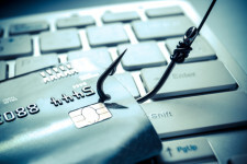 credit card phishing - piles of credit cards with a fish hook on computer keyboard