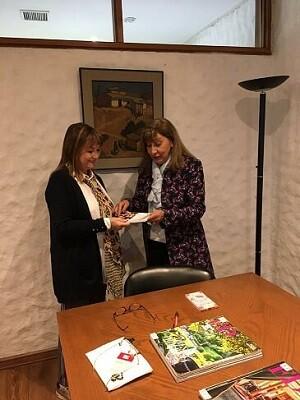Angélica Leal haciendo entrega a Fresia Tremolini de un ejemplar de Cada mirada es única