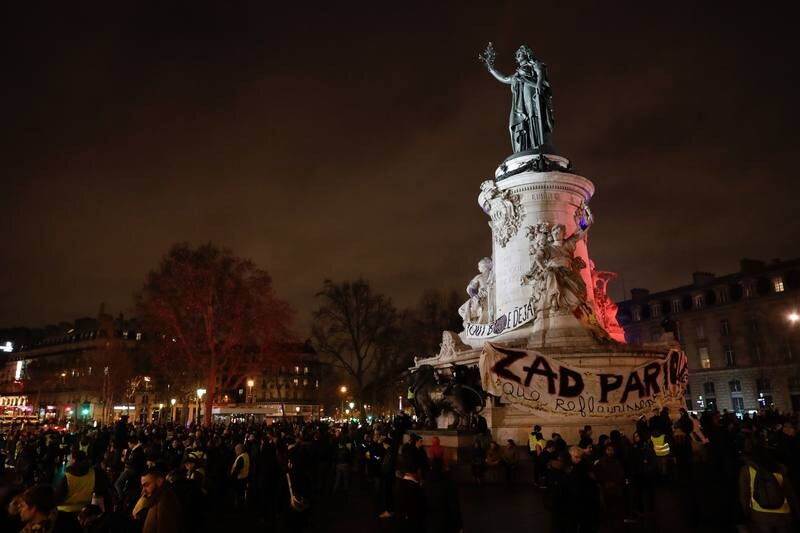 People gather around the statue in place de la Republique in Paris at the end of a march for climate, on December 8, 2018. (Photo by Thomas SAMSON / AFP)