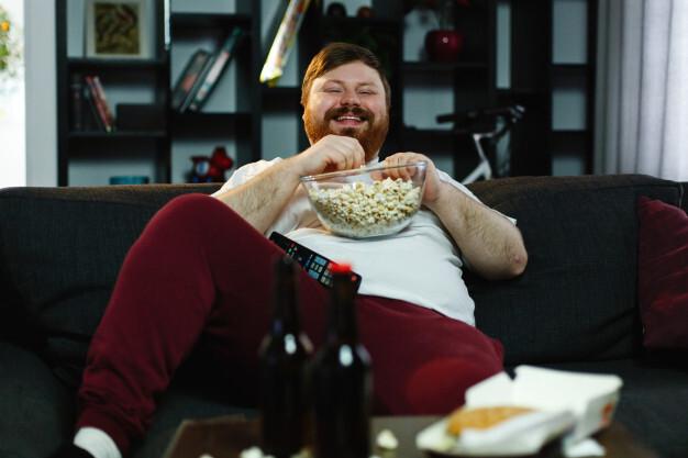 laughing-fat-man-sits-sofa-eats-pop-corn-watches-tv_8353-5508