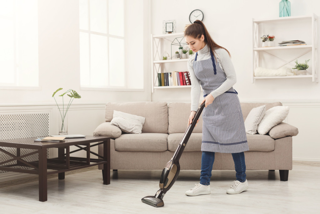 Young woman in uniform cleaning house, washing floor with vacuum cleaner, copy space