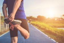 asian-runner-warm-up-his-body-before-start-running-road_30478-199