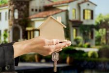 businesswoman-s-hand-holding-wooden-house-model-keys-against-blur-house_23-2148038697