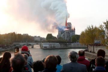 People watch from a bridge as smoke billows from Notre Dame Cathedral during a fire in Paris, France April 15, 2019. REUTERS/Benoit Tessier