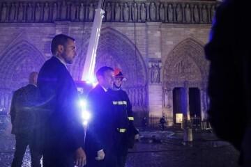 """PHW151. PARÍS (FRANCIA), 15/04/2019.- El presidente de Francia, Emmanuel Macron (c), habla con los bomberos que intentan apagar el incendio de la catedral de Notre Dame este lunes, en París (Francia). Macron proclamó que su intención es """"reconstruir Notre Dame todos juntos"""", y anunció que se lanzará una campaña de recolección de fondos, tanto en Francia como en el extranjero, para ese proyecto. EFE/YOAN VALAT"""