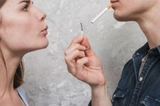 close-up-woman-blowing-match-stick-hold-by-her-boyfriend-carrying-cigarette-mouth_23-2148185369