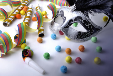 beautiful carnival mask among colorful cotillons on dark and white white backgroung