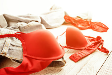 Red lingerie and jeans scattered on the floor. Messy clothes