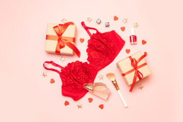 Congratulations on March 8, birthday, Valentines Day. Red women's underwear with black cubes, perfume, red nail polish, powder brush and pink background with space for text.